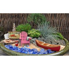 Such a cute mini garden!    Day At The Beach  This beach scene is complete with seagulls, a pail of seashells, flip flops and beach towel. Relax in the adirondack chair or take the canoe out for a spin Plants include miniature white pine, rosemary standard, 'Drunkard's Dream', gold boxwood and blue fescue grass.