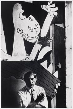 """[Pablo Picasso posing in front of """"Guernica"""" in his studio, Paris]"""