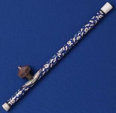 A rare opium pipe adorned with Canton enamel. Within the enamel-covered copper sheath is a peeled stem of bamboo. The endpieces are white jade, and the hexagonal pipe-bowl is ceramic.