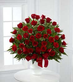 The Soul's Splendor Arrangement's rich display of red roses and lush greens is a perfect way to display the love shared throughout the life of the deceased.