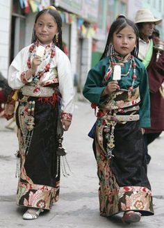 Tibetan sisters in traditional costume walk on a street in Yushu, west China's Qinghai province.