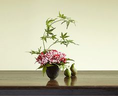 A maple branch arching over a chrysanthemum and sorbus berries in a Japanese style bowl