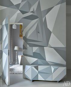 """Фрагмент гостиной. Геометрическая роспись и граненый комод по дизайну Алексея Кио. Потайная дверь ведет в гостевую спальню, где виден фрагмент стола """"Гексагон"""" от студии Archpole."""