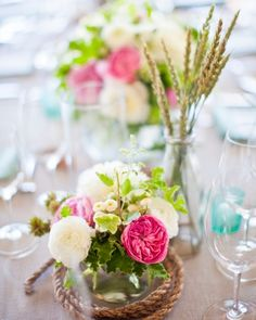 Long tables topped with runners and adorned with a mix of glass gloves filled with flowers and glass cylinders filled with driftwood