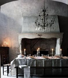 Now that's a dining room! Look at the size of the hearth! I could walk right up in there without bending over! The chandelier is gorgeous and the muted shades of grey against the black furniture just give the room a gothic flair!