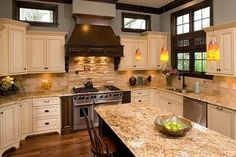 Cream Cabinets with brown glaze, dark accents (LOVE the hood!), tan granite countertops, wood flooring, stone backsplash behind stove. NICE! by deidre