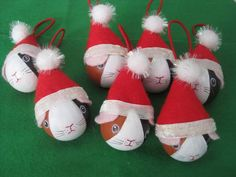 Easy guinea pig Christmas tree ornaments: Wooden craft balls (or ping pong balls) painted to look like guinea pigs, with Santa hats and elastic loop for hanging them.