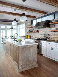 Modern rustic - love the exposed brick, beams, weathered island and open shelving