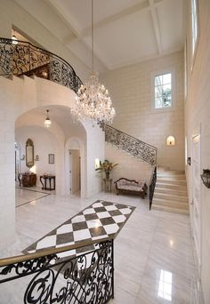 A beautiful chandelier perfectly completes this luxury foyer that features an ample amount of white-washed brick.