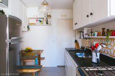 Cozinha compacta tem piso de cimento queimado, bancada de granito e azulejos estampados.