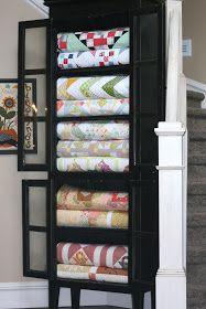 Beautiful home decor idea! Repurpose a curio cabinet to house beautiful quilts.