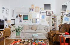Essa sala de estar tem sofá de linho, poltrona de couro e parede recheada de quadros.