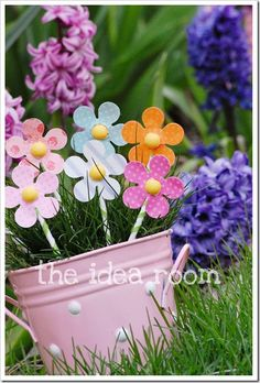 This would be super cute to do with the Daisy scouts in the spring.  Plant grass seeds and make paper flowers to put inside the pots (or tins at Target)