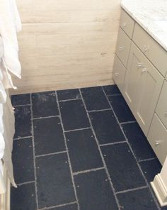 Classic, blue/black Welsh roofing slates installed in a bathroom next to vein cut travertine walls. The feeling of these slates makes you want to grab a piece of chalk and start playing. They are cool. They are recycled. Available at ecofriendlyflooring.com for $3.85/sf.