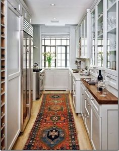 Deep blues and reds pull your eyes towards the rug in an otherwise monochromatic kitchen.