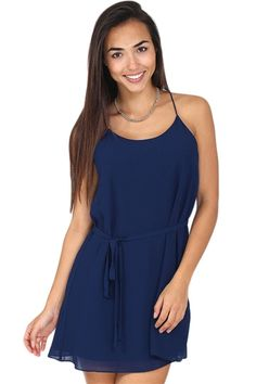 Navy blue chiffon tunic dress featuring stringy racerback, front tie around the waist, and slip underneath. This dress is perfect for any occasion! Pair with cute sandals during the day or pumps and a blazer for the evening.