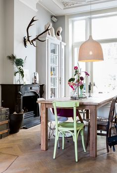 interior, skull, antlers, taxidermy, dining room, wooden floors, fire place, miss matched chais, green, large lamp, large window