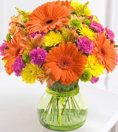 "brightly colored bouquet of orange Gerbera daisies, yellow poms, hot pink mini carnations, and vivid green button poms   $60 bouquet includes 9 stems.  Approximately 11""H x 10""W.  $70 bouquet includes 16 stems.  Approximately 12""H x 12""W. (shown)  $90 bouquet includes 22 stems.  Approximately 13""H x 13""W.	  Approx. 11H x 10W"