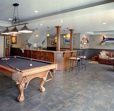 Man cave game room. Nice open feel with pool table and bar. Wheres the TV  maybe knock down wall between playroom and tv room.. ummm