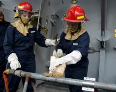 Damage Controlman Vanessa Leigh and Damage Controlman Fireman Sarah Torrey hammer a wooden wedge in place for a soft patch during a simulated flooding drill aboard the amphibious transport dock ship USS Mesa Verde. Small holes or cracks in low-pressure (150 pounds) piping often can be repaired by using what are known as soft patches. #Navy #USNavy #AmericasNavy navy.com