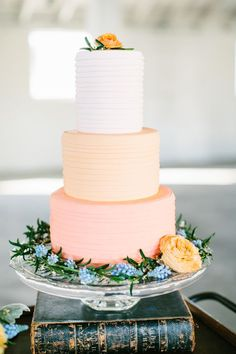 Pretty shades of peach with a small pop of blue in this ombre wedding cake by Baked.