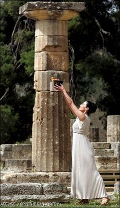 The High Priestess Maria Nafpliotou raises the Olympic flame during the Flame Lighting Ceremony for the Beijing Olympic Games, in Olympia, March 24, 2008