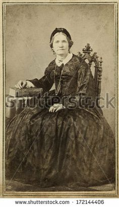 CIRCA 1864 - A vintage Cartes de visite photo of an older pioneer woman. The woman is sitting and is wearing a hoop skirt dress. A photo from the Civil War era. A digital copy of this photo could be purchased at the above web link.