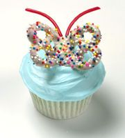 pretzel butterfly with sprinkles on top of cupcake