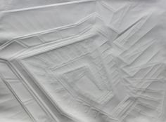 Simon Schubert's haunting paper buildings are produced only by folding the paper – millimeter-scale differences catch and reflect light, creating the illusion of subtle line drawings via implied outlines.