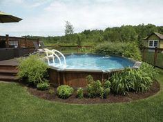 Une piscine hors sol sur une terrasse bois déco avec végétation
