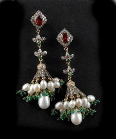A pair of Multi stone chandelier drop earrings, the chandelier sections set with yellow sapphires and diamonds with freshwater pearls and emeralds suspended below surmounted by a double drop of tsavorite garnets and diamonds and terminating with an oval cut almandine garnet and further diamonds all mounted in gold and silver to post fittings