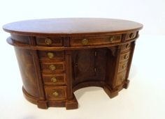 """Patrick Puttock Walnut Desk. A fabulous oval Georgian desk with burled walnut veneers and satinwood inlays, concave kneehole recess with drawer, multiple drawers with satinwood banding, the desk top features four book-matched veneer panels with satinwood inlay and mahogany banding - exquisite. 2.5"""" H, 4.75"""" L, 3"""" D. The desk measures 2"""" from he floor to the bottom of the central drawer. 2"""""""