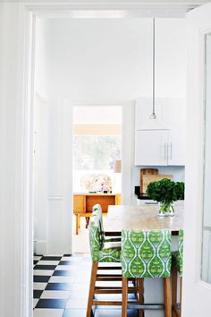 Kitchen dining space with black and white check tiled floor and green upholstered stools.