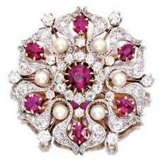 PLATINUM, GOLD, RUBY, DIAMOND AND PEARL BROOCH, PICKSLAY & CO. The stylized flowerhead centering a round ruby weighing approximately .90 carat, framed by six oval-shaped rubies and six pearls measuring approximately 3.2 mm, accented by old European and rose-cut diamonds weighing approximately 2.20 carats, signed Pickslay & Co.; circa 1900.