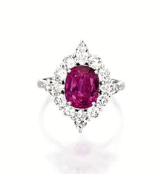 PINK SAPPHIRE AND DIAMOND RING.  Centring on an oval pink sapphire weighing 3.34 carats, framed by brilliant-cut and marquise-shaped diamonds together weighing approximately 1.60 carats, mounted in platinum.