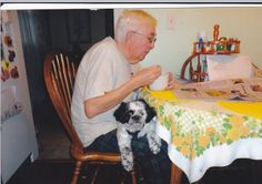 """Bill Sheridan and puppy Susie starting  the day with a bowl of Cherrios,The """"Charleston Daily Mail"""" and a cup of coffee."""