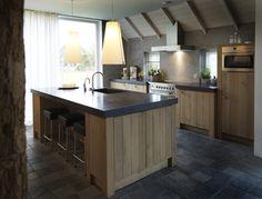 Landelijke keuken met eiland. Eikenhouten keuken met een bijna zwart granieten werkblad