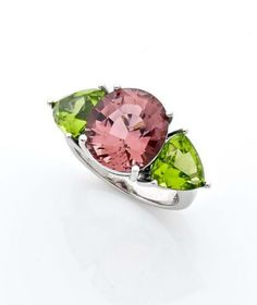 A PINK TOURMALINE, PERIDOT AND WHITE GOLD RING ACCOMPANIED BY AN AIGS CERTIFICATE STATING THAT THE 5,63 CT GEMSTONE IS A NATURAL PINK TOURMALINE