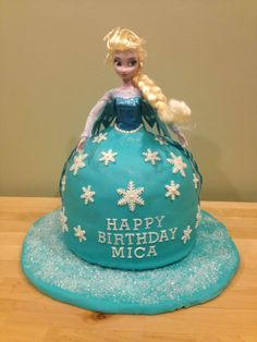 """A Frozen Elsa themed birthday cake.  I baked a cake in a metallic circular mixing bowl, and stacked it on top of an 8"""" cake to made the body of the dress. Carved a hole using a cookie cutter for the doll. Covered the cake with vanilla buttercream, then rolled out homemade marshmallow fondant and covered the """"dress"""".  Stuck the doll in the middle, finished with some snowflake decorations and sparkles."""