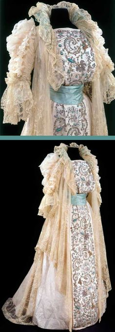Tea gown, House of Rouff, Paris, ca. 1900. Ivory woven silk damask embroidered with glass, metal thread, and beads and purl. Decorated with chain-stitch embroidered net. From the back, a long pleat of lace drops from neck to hem in a style known as the Watteau pleat. Embroidered front panel probably made in India. Victoria & Albert Museum