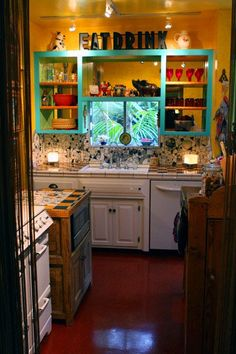 """Artists piece together a colorful look with mosaics in their L.A. bungalow. Beserra-Byrd home in Silver Lake.  The couple's lemon-orange kitchen, dominated by a 1949 O'Keefe & Merritt stove, completes that surge."" Teal shelves. Yellow walls. EAT DRINK sign. Kitchen storage"