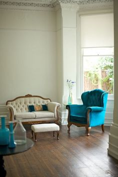 Jewel tone furniture. I love the plain white walls too. Keeps it simple and refreshing for a sitting room.