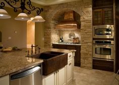 This kitchen features a copper range hood and copper farmhouse sink with a granite island.