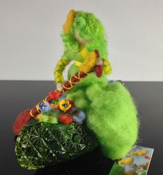 """Midori"" floats along in her green canoe filled with flowers.  She is made of wool fashioned into a collector's pincushion in a vintage pressed glass dish (by Kathleen Dodge-DeHaven)."