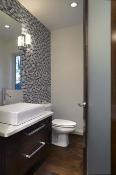 Modern Praire Style home in Atlanta has guest bath with mosaic glass tile wall, floating vanity and rectangular sink. Opaque, glass-panel wood door with lever handle completes the soft modern home look.