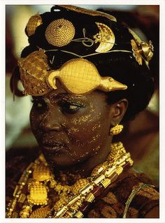 "Africa | Adioukrou Queen Mother ""In Ghana, the display of gold at the Ashanti's king jubilee in 1995 was unsurpassed in splendor. This Adioukrou Queen mother, attending the jubilee, indicates her status by wearing gold turtle and crocodile talismans in her hair. Bedecked with gold jewelry and gold dust makeup, she exhibits her husband's authority and worth."" Photo by Carol Beckwith and Angela Fisher"