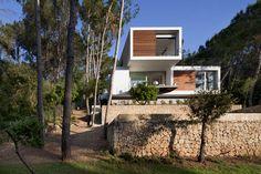 En el exterior se visualiza una composición de cubos de líneas puras en armonía con su entorno natural, situado en Pollensa Mallorca