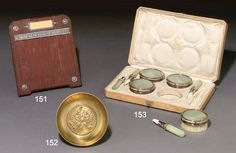 A bowenite and enamelled two-colour gold-mountedcoffret à jeux by Fabergé and with the workmaster's intials of Michael Perchin, St. Petersburg, circa 1890, with scratched inventory number 55879 Comprising four circular brushes and four cylindrical chalk holders of bowenite, with red guillloché enamel ribbon-tied chased and engraved laurel mounts, within reeded bands,fully marked, the brushes marked Fabergé, the chalk holders with workmaster's initials, in fitted wood case stamped in…