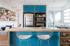 Cozinha integrada com marcenaria revestida de fórmica azul e balcão para refeições rápidas.
