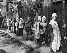 Okay, let's form a line single file.......looks like an old photo of elementary school kids costumed for Halloween.